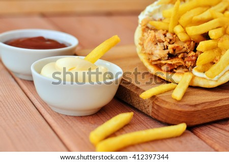French fries dipped in white sauce. Gyro meat and french fries on a wooden table - stock photo
