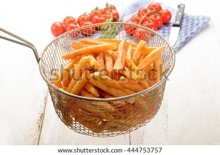 french fries from the fryer in a sieve and fresh tomato in the background