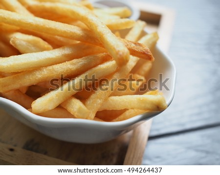 French fries in a bowl on a wooden background