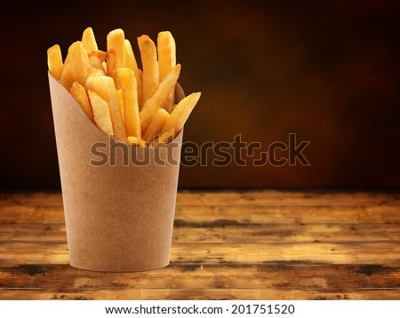 french fries in a paper basket on wooden table - stock photo