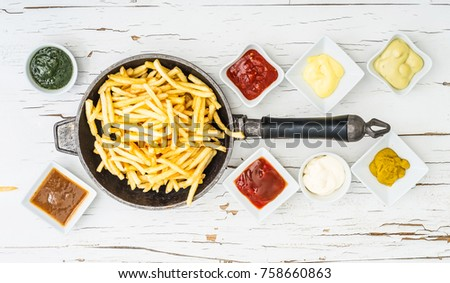 French fries in frying pan with different sauces in white saucers on white wooden background with cracked paint. Top view. View from above.