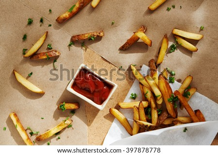 french fries in paper bag and red sauce. top view - stock photo