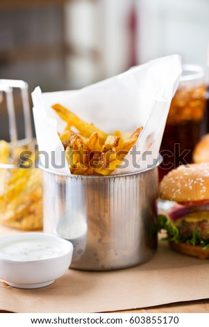 french fries in paper wrap with hamburger for meal
