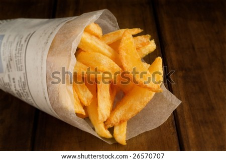 French fries in rolled newspaper packet or packaging - stock photo