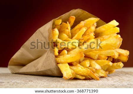French fries in the paper bag on burned backdrop on wooden table - stock photo