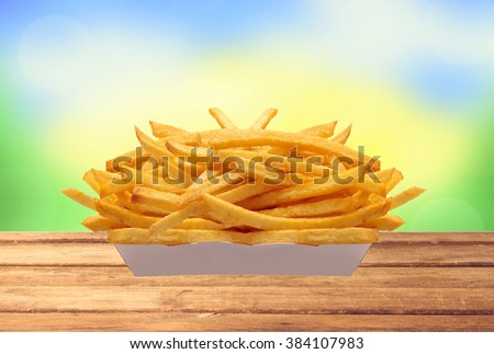 French fries in white box on table over nature background