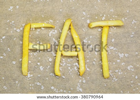 French fries inscription FAT with salt around - stock photo