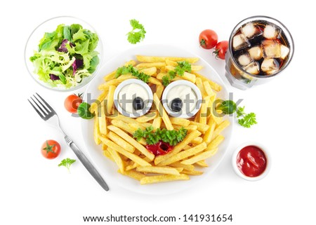 French fries meal with a funny face, salad and soda - stock photo