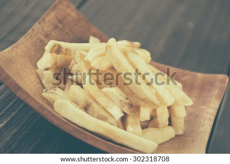 french fries on wood background - soft focus with vintage film filter