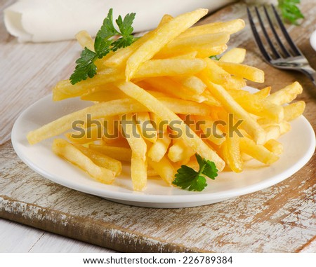 French fries on  wooden board. Selective focus - stock photo