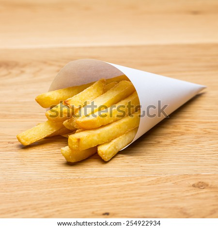 french fries pommes bag on a wood background - stock photo