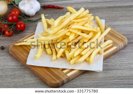 French fries potato on the wood background - stock photo