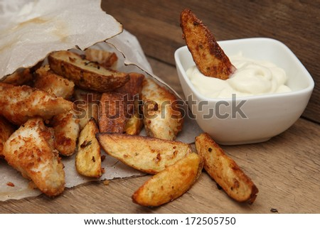 French fries potato wedges in recycled kraft paper bag on wooden old background. Fast food. Closeup. Potatoes with gravy - stock photo