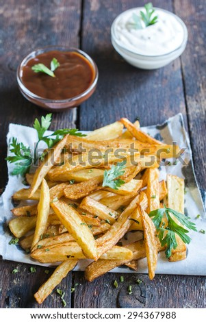 French fries served on wooden table with sauces in background,selective focus  - stock photo
