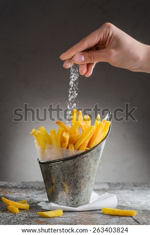 French fries sprinkled with salt in an iron bucket - stock photo