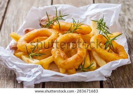 french fries with calamari and rosemary on white paper