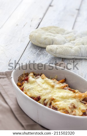 french fries with chilli au gratin in a caserole on a rustic white table