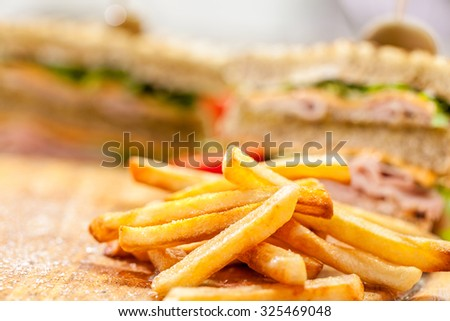 french fries with club sandwich on wooden background - stock photo