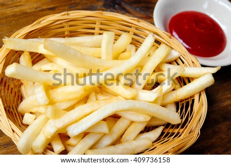 French fries with ketchup on wood background. - stock photo