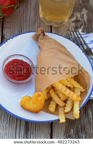 French fries with ketchup. On wooden table. Natural light, selective focus.