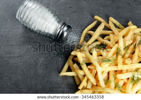 french fries with salt and dill on table - stock photo