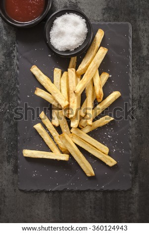 French fries with sea salt and ketchup, on black slate.  Overhead view.