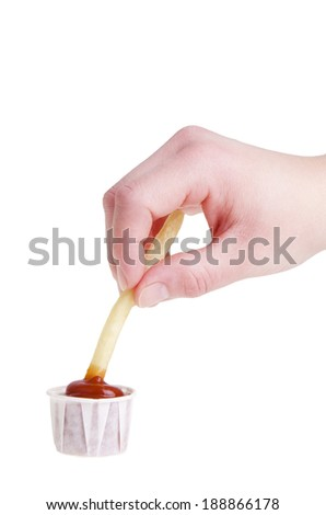French fry being dipped in ketchup over white  - stock photo