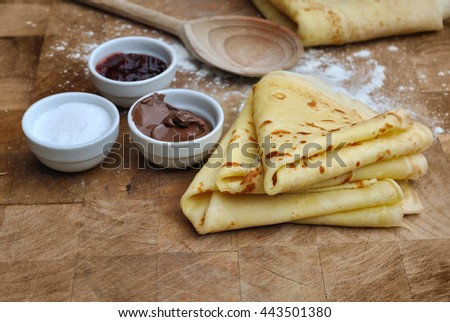 french homemade pancakes with accompaniments on wooden plank - stock photo