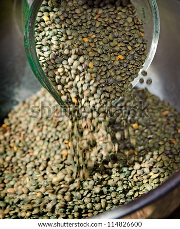 French lentils pouring into a stainless steel bowl