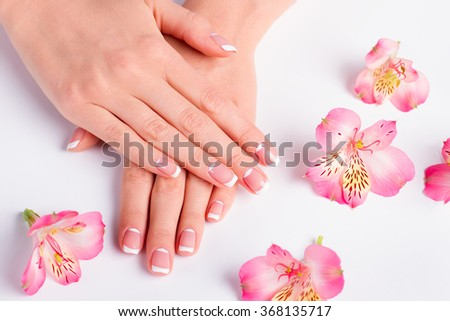 French lunar manicure with beautiful pink freesias close-up.