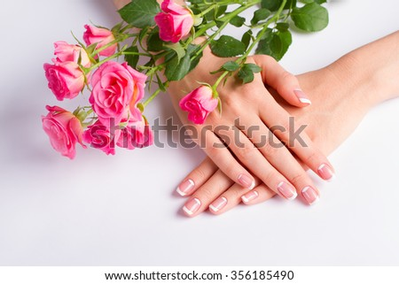 French lunar manicure with bouquet of beautiful pink roses close-up.