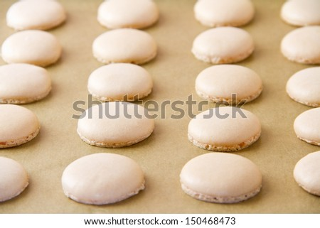 French macaron shells (pronounced macaroon, a popular buttercream filled meringue type cookie or biscuit) on baking sheet lined with baking parchment paper.