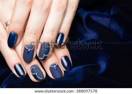 French manicure - beautiful manicured female hands with blue manicure with rhinestones on dark blue background - stock photo