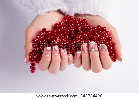 French manicure on a background of red beads. Beautiful bright beads in women's hands. Christmas necklace. - stock photo