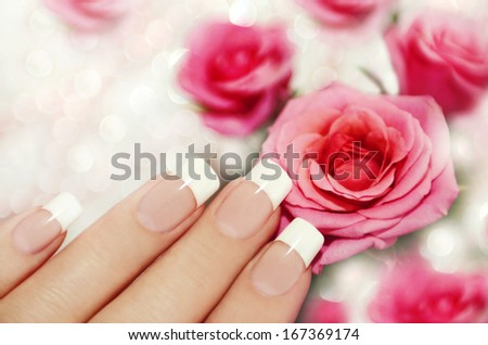French manicure on a woman's hand with pink roses on a brilliant background. - stock photo