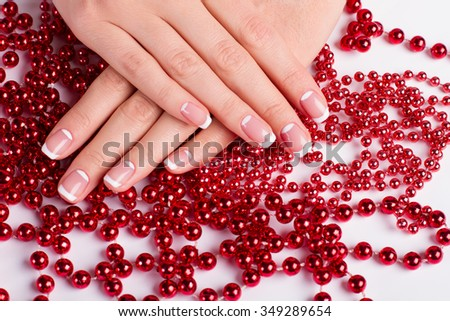 French manicure on red beads. Beautiful well-groomed female hands on red beads. - stock photo