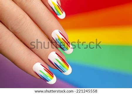 French manicure with bright colored stripes on the background. Rainbow manicure. - stock photo