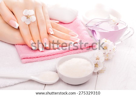 french manicure with essential oils, apricot flowers. spa - stock photo