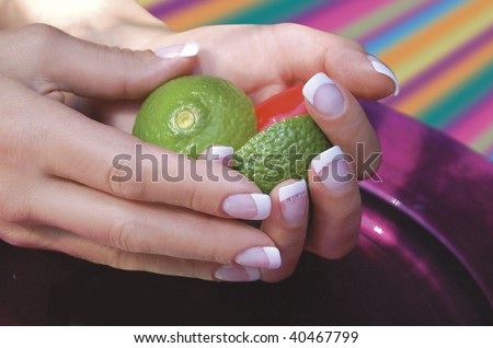 French Manicured hands holding lemon and lime