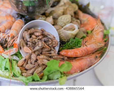 French Mixed Cold Seafood platter (Plateau de fruits de mer) with Lime, Ice and parsley on vegetable and seaweed in line buffet for party in Paris, France. Selective Focus - stock photo