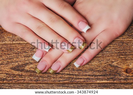 French nail art in gold color on wooden background