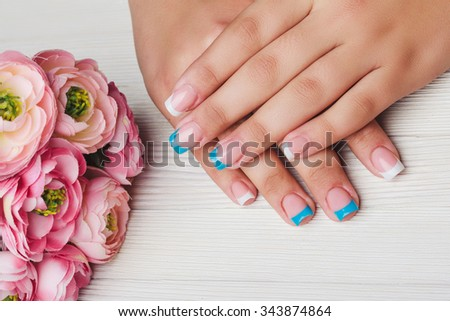 French nail art in light pink color on wooden background