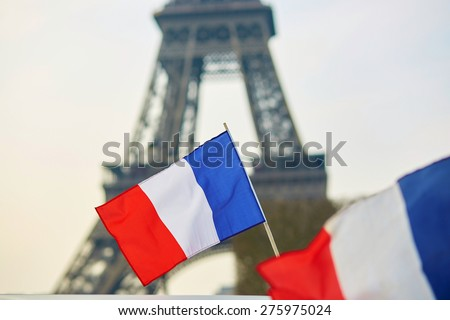 French national flag (tricolour) in Paris with the Eiffel tower in the background - stock photo