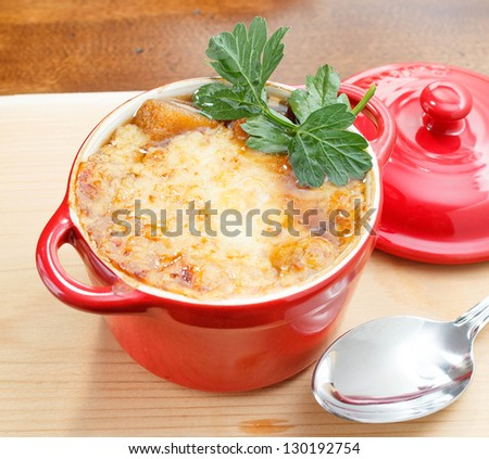 French Onion Soup Gratin in red pot on table top - stock photo
