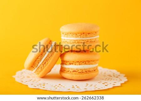 French orange macarons on orange background - stock photo