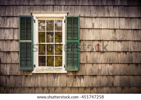 French pane window with green shutters on a wood cedar shingle shake home exterior.  - stock photo
