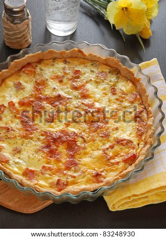 french pie Quiche Lorraine on the table with flower - stock photo