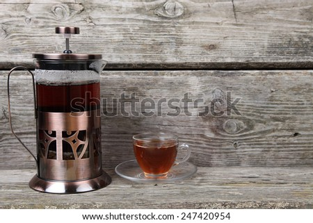 French-press and cup of tea on old wooden table - stock photo
