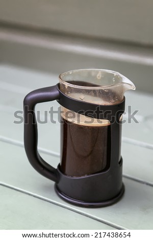 French Press/Cafetiere containing freshly brewed Coffee in an outdoor setting.  - stock photo