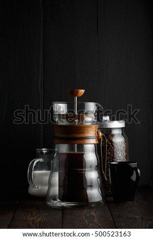 French press with coffee, coffee beans in the pot, milk jug, dark.
